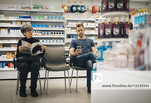 Customers sitting on chairs against medicine rack at pharmacy store