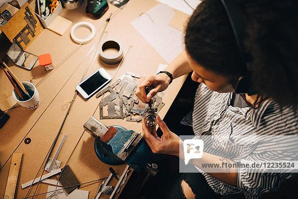 Hochwinkelansicht des Technikers bei der Arbeit am Schreibtisch in der Werkstatt