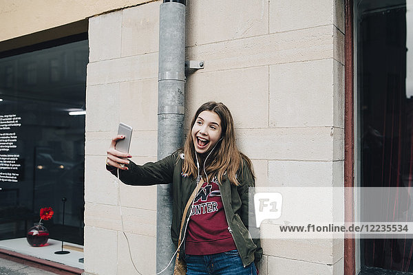 Happy girl with open mouth taking selfie through smart phone while standing against wall
