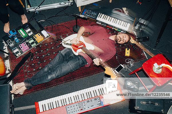 Hochwinkelansicht eines Mannes  der Gitarre spielt  während er im Studio auf dem Teppich liegt.