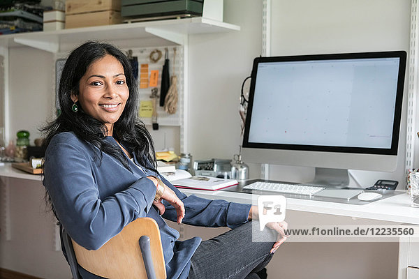 Portrait of smiling businesswoman sitting at desk in home office