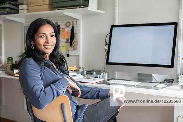 Porträt einer lächelnden Geschäftsfrau am Schreibtisch im Home Office