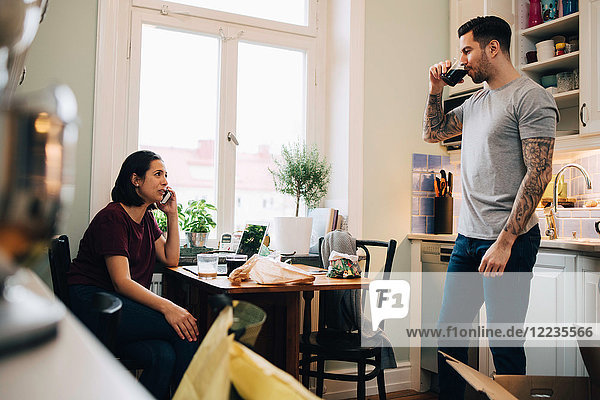 Woman using smart phone while man having drink at kitchen during relocation