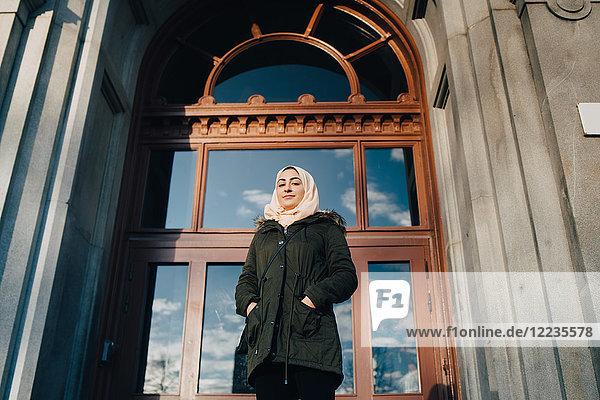 Flachwinkel-Porträt einer selbstbewussten jungen Muslimin  die mit den Händen in den Taschen vor der Tür steht.