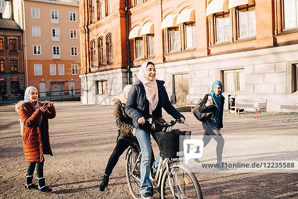 Junge Frauen fotografieren Teenagermädchen beim Radfahren mit Freund gegen Bauen in der Stadt