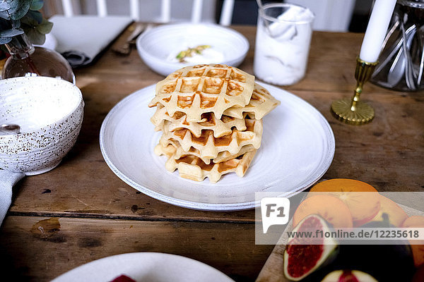 High angle close-up of waffles stacked in plate on wooden table