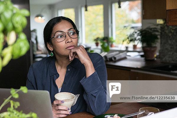 Nachdenkliche Geschäftsfrau beim Sitzen mit Laptop auf dem Tisch im Home Office