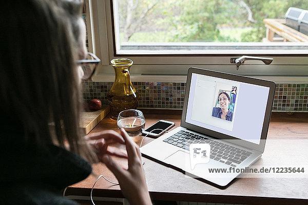 High-Winkel-Ansicht der Geschäftsfrau Videogespräche weiblichen Kollegen auf dem Laptop im Home-Office
