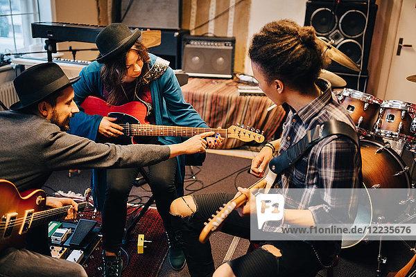Mann  der eine Freundin unterrichtet  während er im Aufnahmestudio Gitarre spielt.