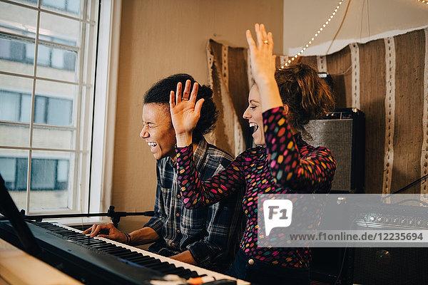 Glückliche Freunde beim Klavierspielen und Üben im Aufnahmestudio