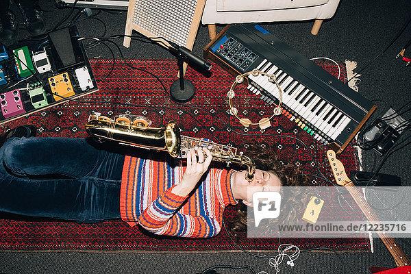 Hochwinkelansicht einer lächelnden Frau  die Saxophon spielt  während sie im Studio auf dem Teppich liegt.
