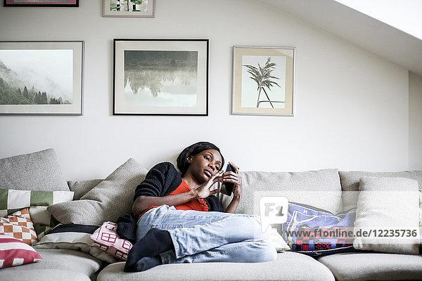Volle Länge der Frau  die das Handy benutzt  während sie zu Hause auf dem Sofa liegt.