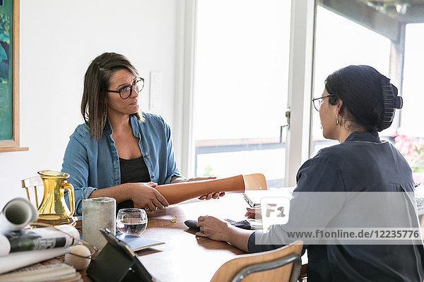 Weibliche Designprofis diskutieren am Tisch im Home-Office