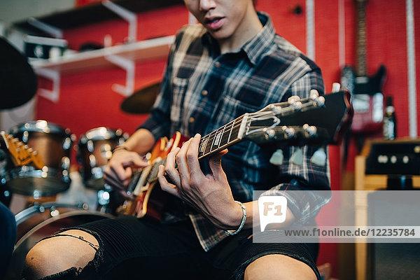 Mittelteil des Mannes  der Gitarre spielt  während er im Aufnahmestudio sitzt.