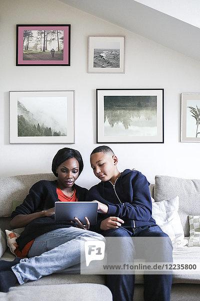Mutter und Sohn mit digitalem Tablett auf dem Sofa zu Hause