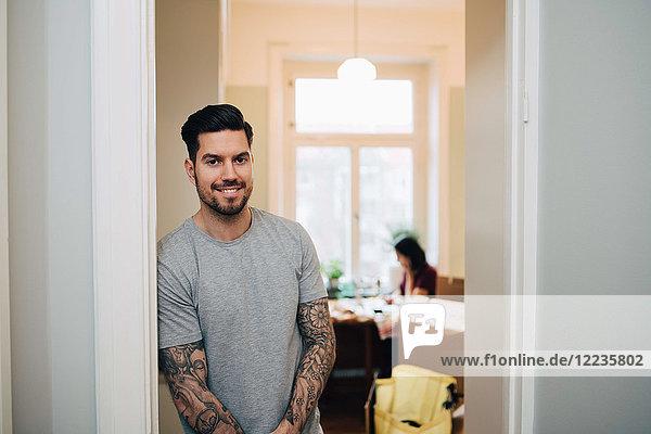 Porträt eines lächelnden Mannes  der sich an die Tür des neuen Hauses lehnt.