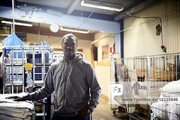 Portrait of confident mid adult volunteer standing in warehouse