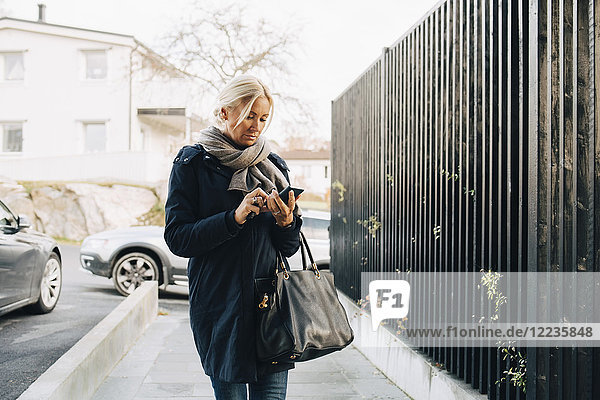 Mature woman using smart phone while walking on footpath by fence