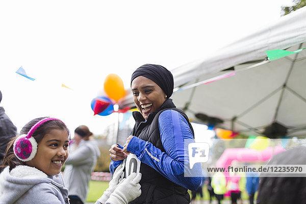Lächelnde Tochter beim Marathon-Lätzchen auf Mutter beim Benefizlauf