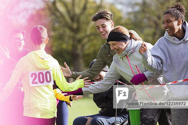 Zuschauer High-Five-Läufer beim Charity-Lauf im Park