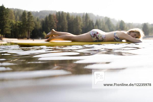 Gelassene Frau  die auf einem Paddelbrett auf einem ruhigen See liegt.