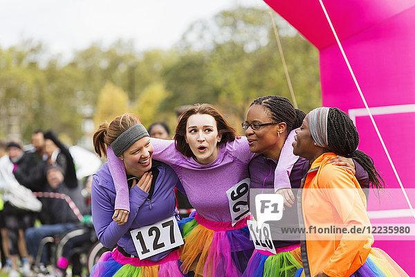 Fröhliche Läuferinnen umarmen sich beim Charity-Lauf.