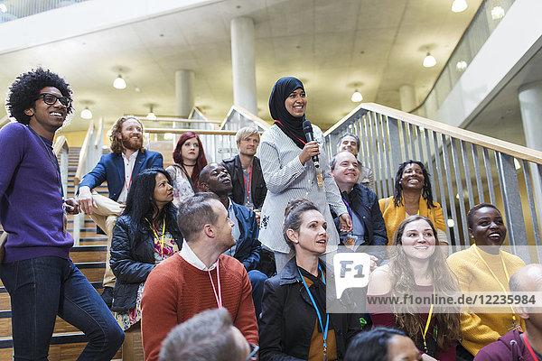 Lächelnde Frau im Hijab im Gespräch mit Mikrofon im Konferenzpublikum
