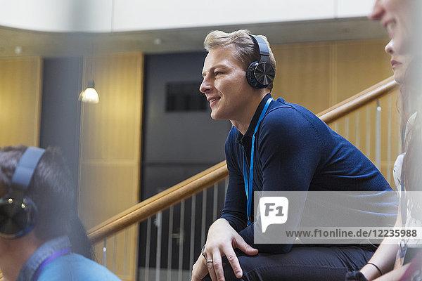 Lächelnder  aufmerksamer Mann  der Kopfhörer im Konferenzpublikum hört.