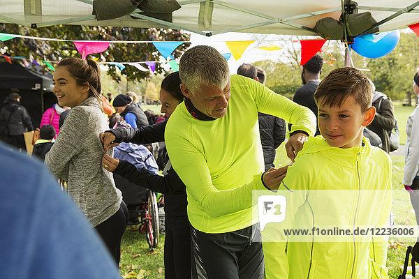 Vater pinnt Marathon-Lätzchen auf Sohn beim Benefizlauf im Parkzelt