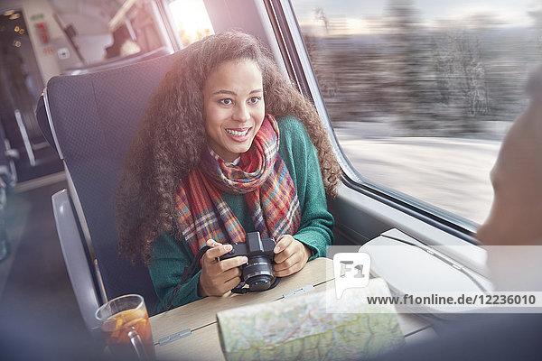 Lächelnde junge Frau mit Kamera und Karte im Personenzug
