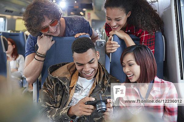 Junge Freunde beim Betrachten von Fotos auf der Digitalkamera im Personenzug