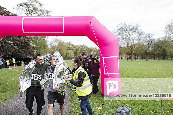 Volunteer wickelt männliche Läufer in Thermodecke im Marathon-Ziel ein.