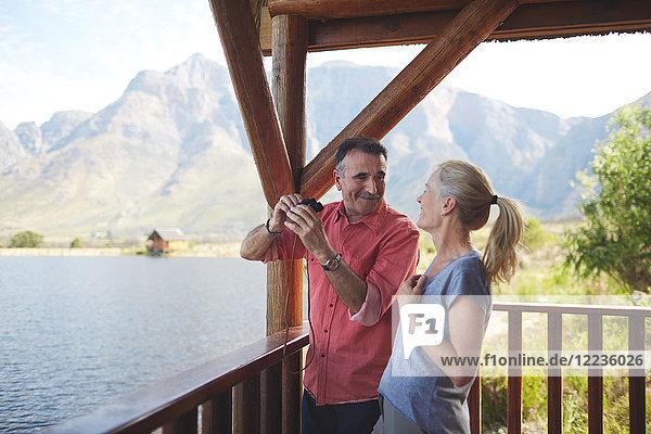 Glückliches Paar mit Fernglas mit Seeblick vom Balkon aus