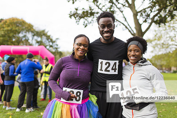 Portrait lächelnde  selbstbewusste Familie mit Marathon-Lätzchen beim Benefizlauf im Park