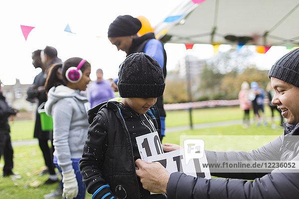 Vater pinnt Marathon-Lätzchen auf Sohn beim Benefizlauf im Park
