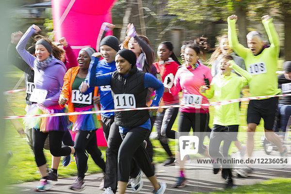 Begeisterte Läufer jubeln und rennen beim Charity-Lauf im Park