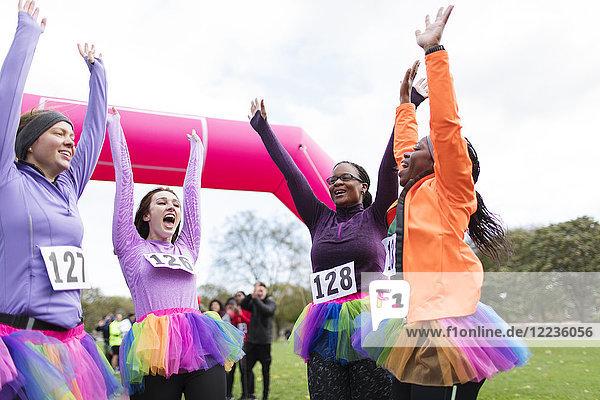 Begeisterte Läuferinnen im Tutus jubeln  feiern beim Charity-Lauf im Ziel