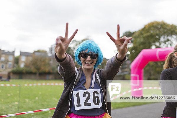 Portrait begeisterte Läuferin in Perücke gestikulierend Friedenszeichen beim Charity-Lauf im Park