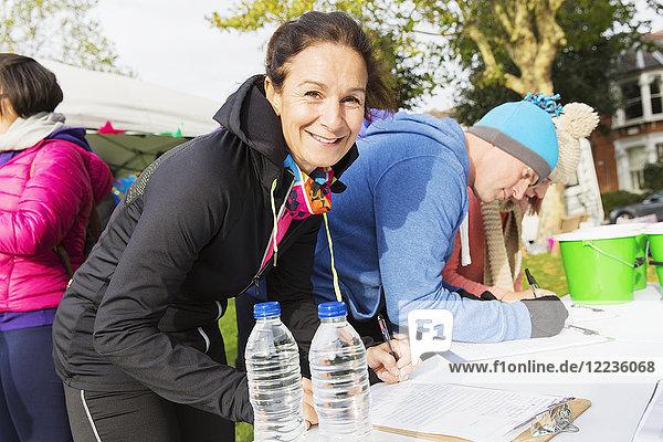 Portrait lächelnde Läuferin beim Einchecken beim Charity Run im Park