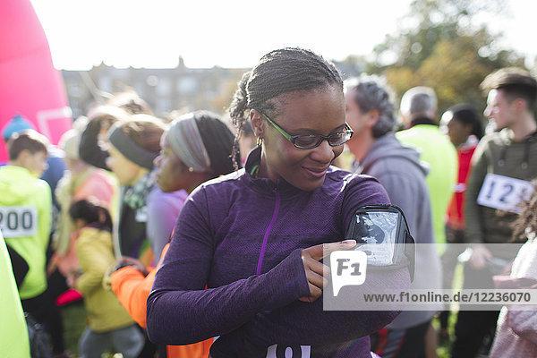 Läuferin bereitet Musik auf mp3-Player-Armband beim Benefizlauf vor