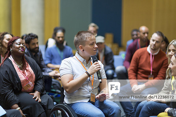 Sprecherin im Rollstuhl mit Mikrofon im Gespräch mit dem Publikum