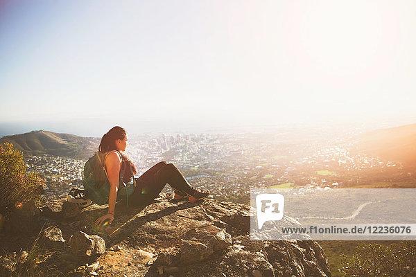 Serene Backpackerin sitzt auf Felsen über der sonnigen Stadt