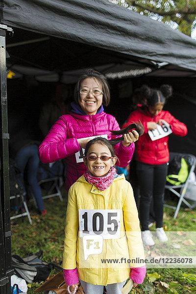 Portrait lächelnde  selbstbewusste Mutter und Tochter Läufer im Charity-Laufzelt