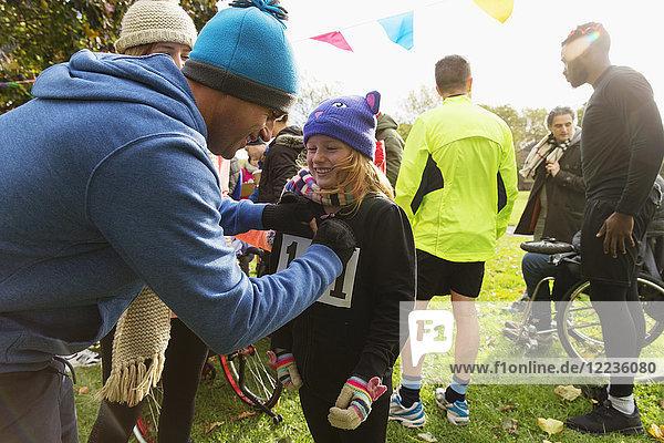 Vater pinnt Marathon-Lätzchen auf Tochter beim Benefizlauf im Park