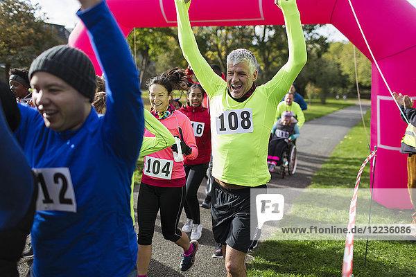 Begeisterte Läufer jubeln  überqueren die Ziellinie des Wohltätigkeitslaufs