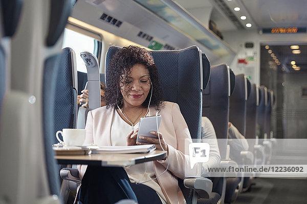 Geschäftsfrau beim Arbeiten und Musikhören mit Kopfhörer und Smartphone im Personenzug