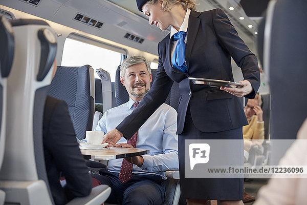 Frau  die dem Geschäftsmann im Personenzug Kaffee serviert.