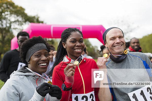 Portrait lächelnde Läufer mit Medaillen beim Benefizlauf