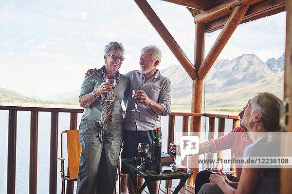 Glückliche aktive Seniorenpaare beim Weintrinken auf dem Sommerbalkon