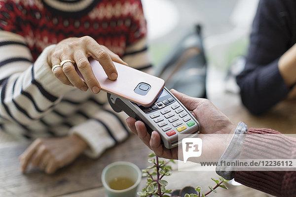 Frau mit Smartphone mit kontaktloser Bezahlung